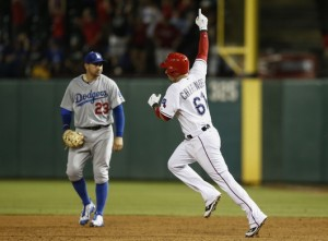 Jun 16, 2015; Arlington, TX, USA; Texas Rangers catcher Robinson Chirinos (61) points as he circles the bases on his walk-off solo home run in front of Los Angeles Dodgers first baseman Adrian Gonzalez (23) during the ninth inning of a baseball game at Globe Life Park in Arlington. The Rangers won 3-2. Mandatory Credit: Jim Cowsert-USA TODAY Sports