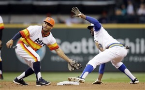 Houston Astros second baseman Jose Altuve, left, and Seattle Mariners' James Jones both look for the call after Jones stole second base in the second inning of a baseball game Saturday, May 24, 2014, in Seattle. (AP Photo/Elaine Thompson)