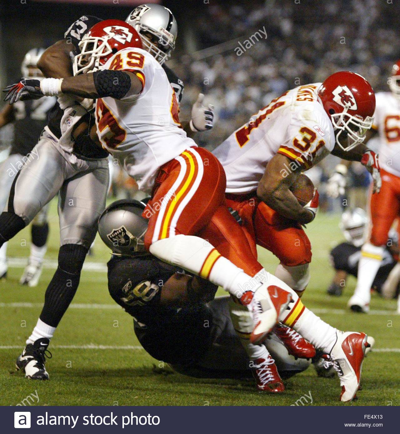 Kansas City Chiefs' Priest Holmes (R) runs in for a first down fourth quarter as teammate Tony Richardson (L, 43) blocks Oakland Raiders' Anthony Dorsett (Top L) and Napoleon Harris (Bottom C) on Monday, 20 October 2003 at Network Associates Coliseum in Oakland, California. EPA/Arleen NG